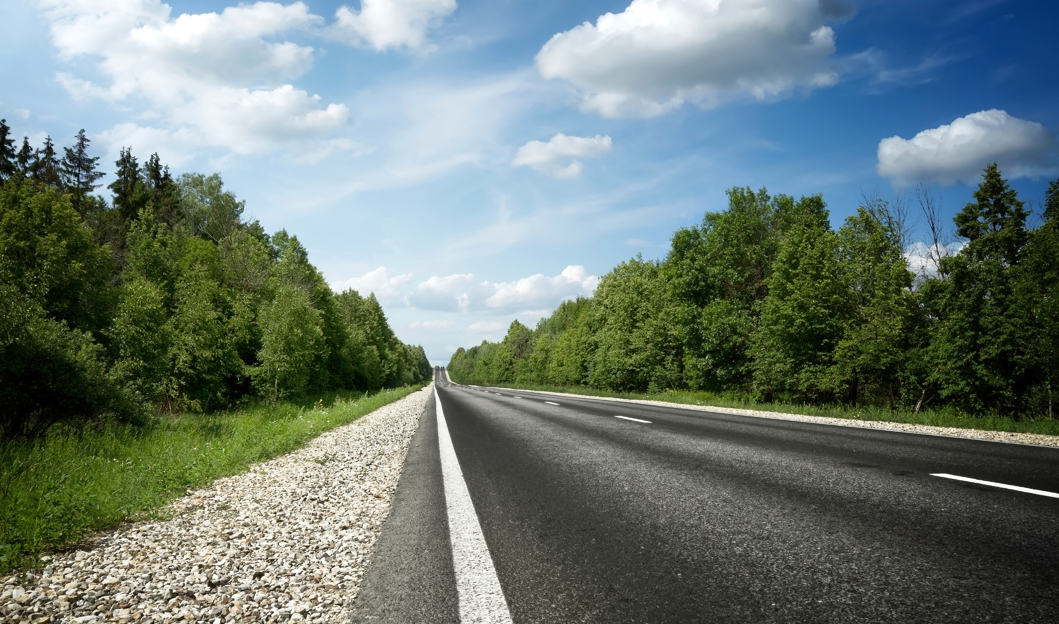 Lege autoweg door landschap met blauwe lucht