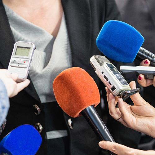 Serveral microphones and recording devices held near a professionally dressed woman
