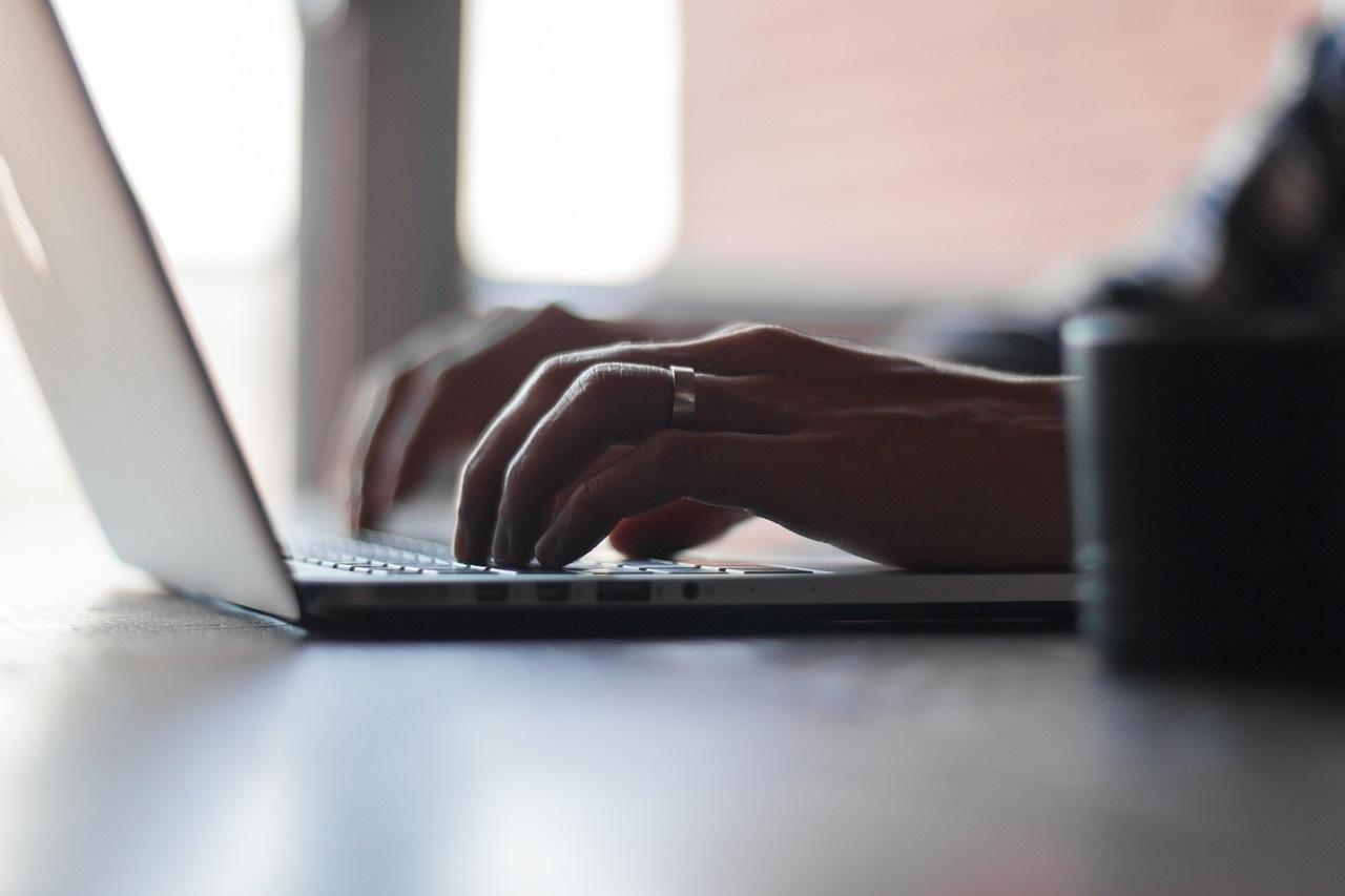 handen die typen op een laptop
